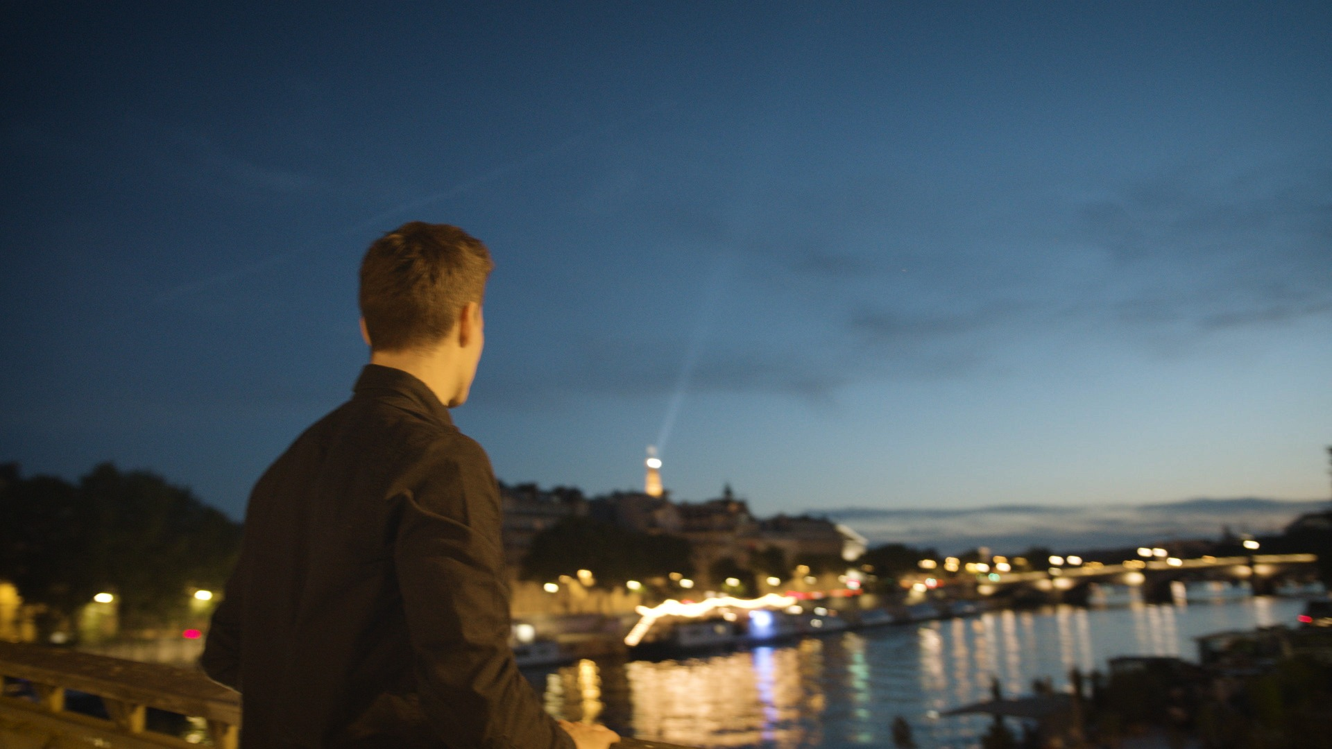 young videographer looking at the horizon in Paris evening