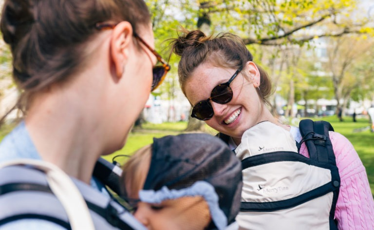 two women smiling with their baby carrier